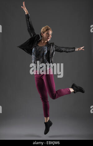 Studio shot of cheerful woman jumping with arms raised - Stock Photo