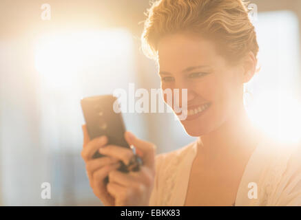 Smiling young woman using mobile phone - Stock Photo