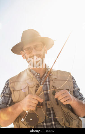 Portrait of man holding fishing rod - Stock Photo