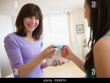 Mom giving teenage girl (14-15) credit card - Stock Photo