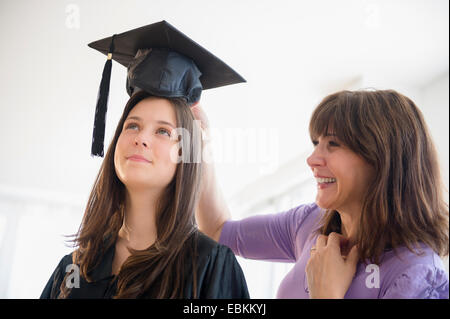 Teenage girl (14-15) getting ready for graduation ceremony - Stock Photo