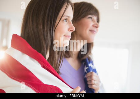 Teenage girl (14-15) and her mom wrapped in American Flag on Fourth of July - Stock Photo