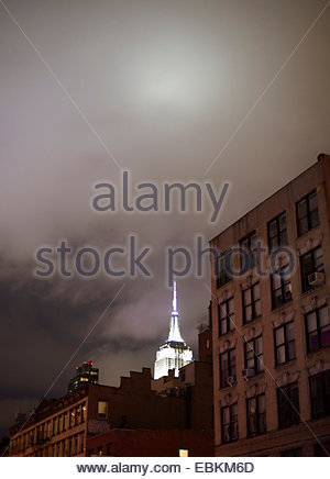 The Empire State Building illuminated at night with buildings in foreground New York USA - Stock Photo