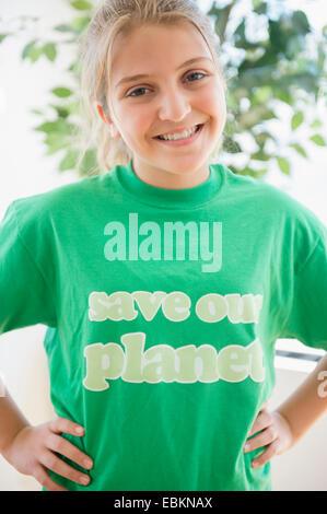 Portrait of smiling teenage girl (12-13) wearing green t-shirt - Stock Photo