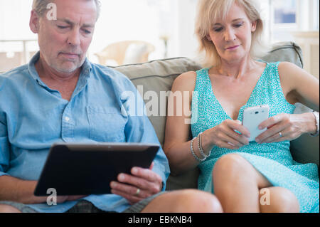 Portrait of couple sitting on sofa using digital tablet and smart phone - Stock Photo