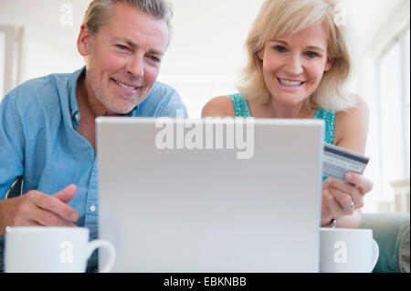 Portrait of couple using laptop, with credit card in view - Stock Photo