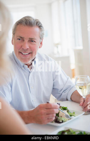 Portrait of man eating and drinking white wine at restaurant - Stock Photo
