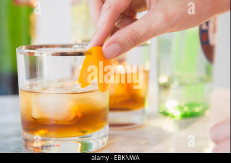 Close-up shot of bartender's hand decorating cocktail glass with orange peel - Stock Photo