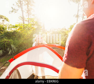 USA, Florida, Tequesta, Couple setting up tent in forest - Stock Photo