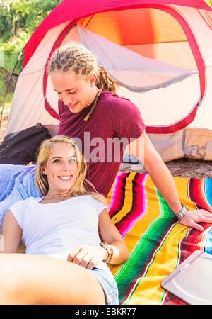 Couple resting in front of tent - Stock Photo
