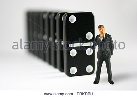 figure in front of a row of dominoes - Stock Photo