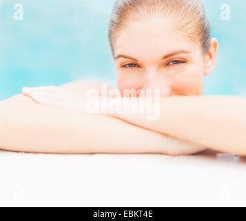 Portrait of woman on edge of swimming pool - Stock Photo