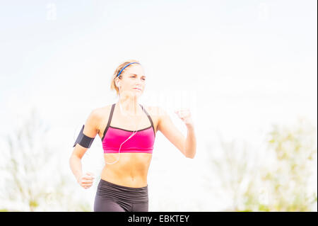 Young woman jogging in park - Stock Photo