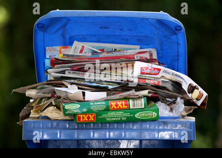 filled, blue refuse container for used paper, Germany, North Rhine-Westphalia - Stock Photo