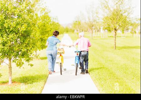 USA, Florida, Jupiter, Rear view of couple wheeling bicycles along cycling path - Stock Photo