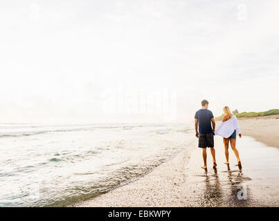 USA, Florida, Jupiter, Young couple walking along surf line of sandy beach, holding hands - Stock Photo
