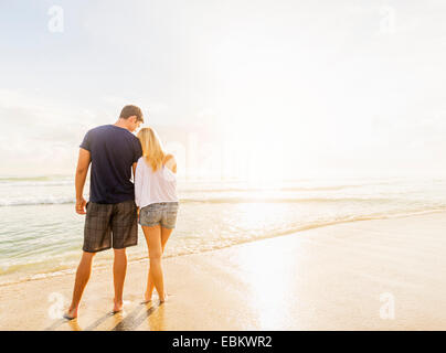 USA, Florida, Jupiter, Rear view of young couple standing side by side on sandy beach, looking at sea - Stock Photo