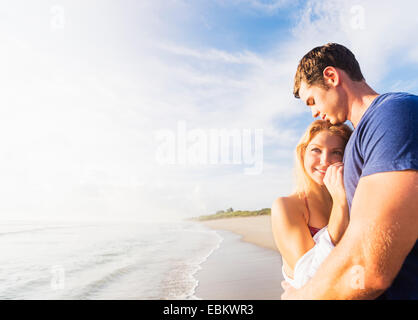 USA, Florida, Jupiter, Portrait of young couple embracing on sandy beach, against background of coastline - Stock Photo