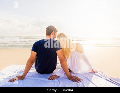 USA, Florida, Jupiter, Rear view of young couple sitting on blanket on sandy beach, looking at sea - Stock Photo