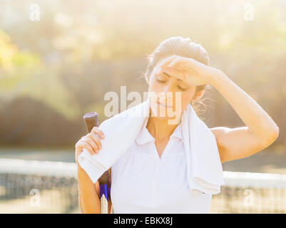 Portrait of young woman with towel and tennis racket wiping forehead with back of hand - Stock Photo