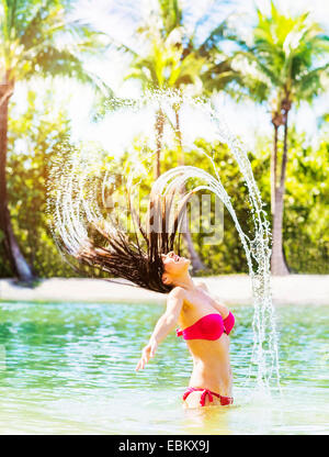 USA, Florida, Jupiter, Portrait of young woman wearing bikini tossing hair and splashing water in tropical lagoon - Stock Photo