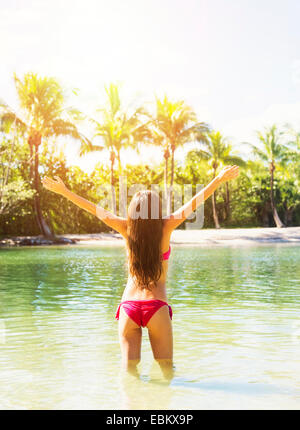 USA, Florida, Jupiter, Rear view of young woman wearing bikini standing in waters of tropical lagoon, raising arms - Stock Photo