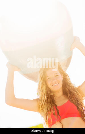 USA, Florida, Jupiter, Portrait of young woman holding surfboard over head - Stock Photo