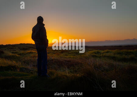 Sunset silhouette in Southport, Merseyside, UK. 2nd December, 2014.  Silhouetted man. UK Weather as seen at Ainsdale - Stock Photo