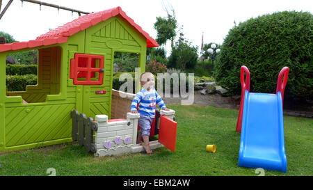 little boy playing in a garden with slide and a Wendy house - Stock Photo