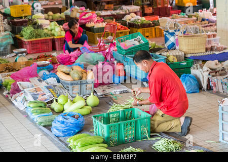 Man laying out food produce in covered market, Miri, Malaysia - Stock Photo