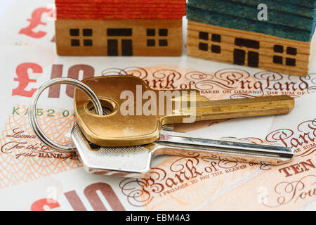 House door keys on money sterling ten pound notes GBP with two houses to illustrate property ladder and portfolio - Stock Photo