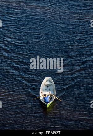 Man rowing a small fiberglass rowboat - Stock Photo