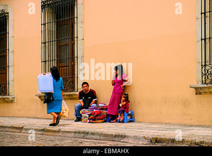 Street trader with husband and child on a street in Oaxaca City Mexico. - Stock Photo