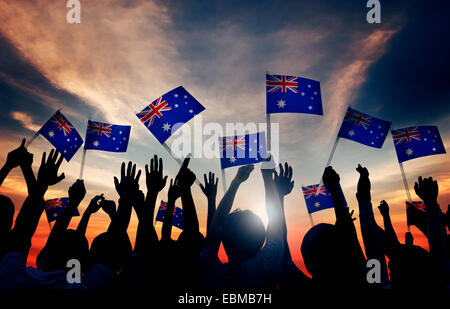 Group of People Waving Australian Flags in Back Lit - Stock Photo