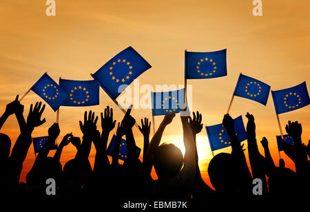 Group of People Waving European Union Flags in Back Lit - Stock Photo
