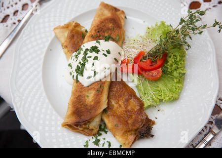 Krakow, Poland; Polish food, spinach pancakes with garlic sauce. - Stock Photo