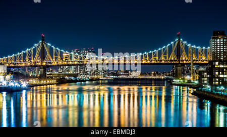 Ed Koch bridge (aka Queensboro bridge) as viewed by night from Roosevelt Island bridge in Queens, New York - Stock Photo