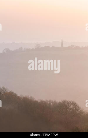The silhouette of the Obelisk at Eastnor can be seen through the fog from British Camp on the Malvern Hills. - Stock Photo