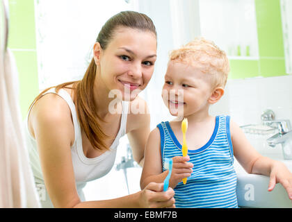 mother with child boy brushing teeth - Stock Photo