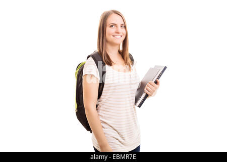 Back to school, finally! Young girl carrying a backpack, some books while going to school, isolated on white background. - Stock Photo