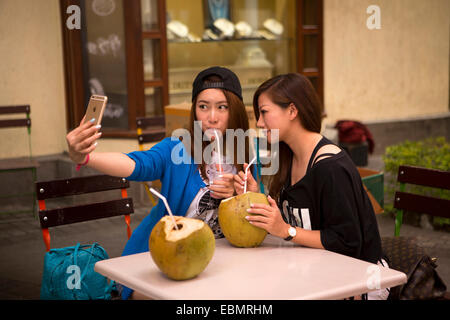 Mauritius, Port Louis, Caudon Waterfront, young girl Chinese tourists taking selfie on iPhone - Stock Photo