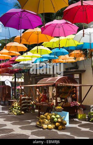 Mauritius, Port Louis, Caudon Waterfront, drink seller in shade below colourful shading umbrellas - Stock Photo