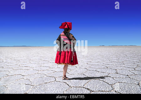 Rear view of bolivian woman with folklore dress  in the desert of Uyuni, Bolivia - Stock Photo