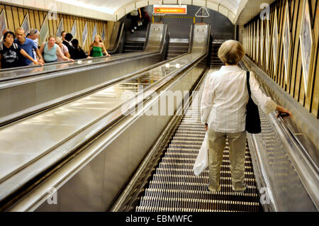Budapest, Hungary. Woman going down an escalator in the metro - Stock Photo