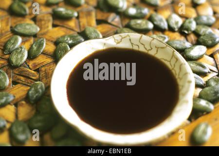 styrian pumpkin, styrian oil pumpkin (Cucurbita pepo var. styriaca), seeds and boal with pumpkin oil - Stock Photo