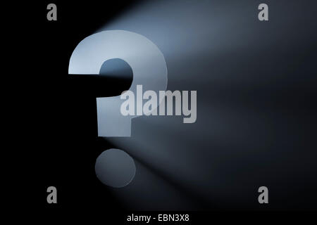 Question Mark. Hole cut in cardboard, smoke machine and spotlight. The image may appear noisy, but that is the texture - Stock Photo