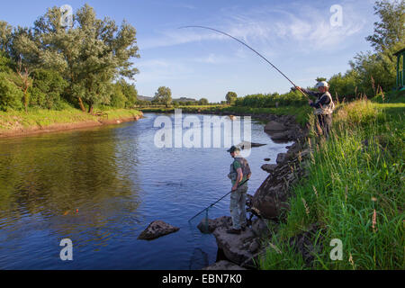 Atlantic salmon, ouananiche, lake Atlantic salmon, landlocked salmon, Sebago salmon (Salmo salar), two anglers fishing - Stock Photo