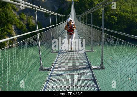 female wanderer on suspension bridge over lake Lac de Monteynard-Avignonet, France, Grenobl - Stock Photo