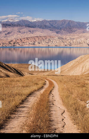 path to storage lake in hilly landscape, snow-covered mountain range in background, Kyrgyzstan, Djalalabad, Taskoemuer - Stock Photo