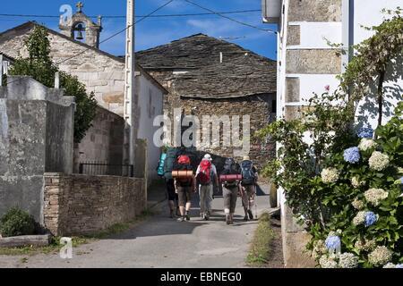 pilgrims on the way in Gonzar, Spain, Galicia, Lugo, Gonzar - Stock Photo